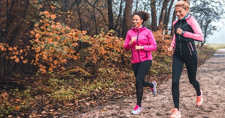 Two women running in park to calm dental nerves and anxiety